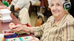 A senior citizen woman playing Bingo with Silent Sound System headphones