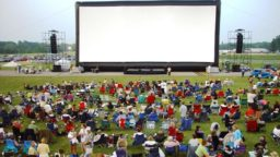 A crowd sitting in front of an outdoor movie screen