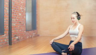 Woman sitting cross-legged on yoga mat with Silent Sound System headphones on